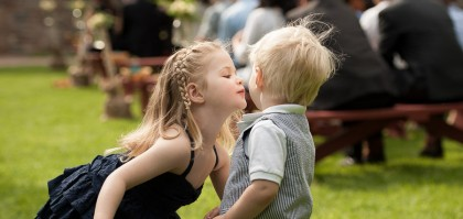Little Girl Kissing Little Boy at Wedding