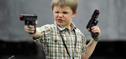 LAS VEGAS, NV - MARCH 30:  A young boy plays with a toy gun at the ACM Experience at the Mandalay Bay Resort & Casino on March 30, 2012 in Las Vegas, Nevada.  (Photo by Jerod Harris/ACMA2012/Getty Images for ACM)